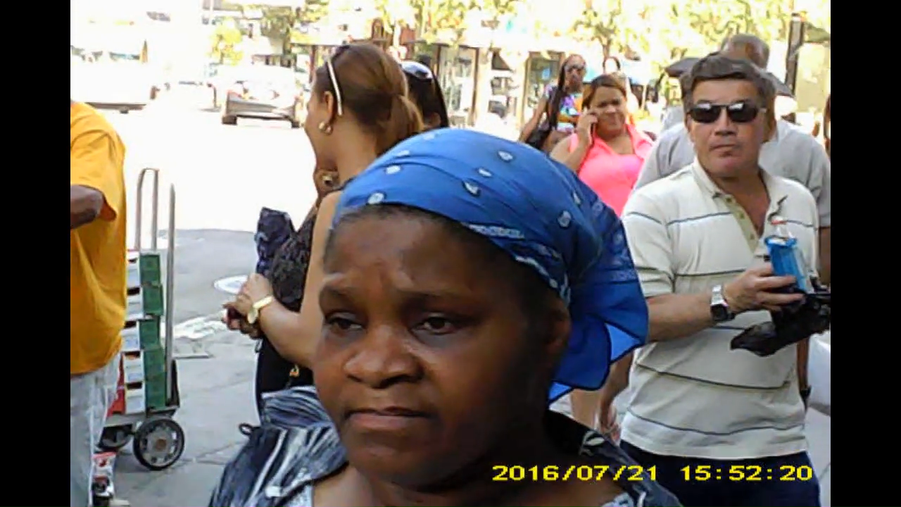 Closeup of older female and man with sun glasses. What is he holding? Could it be one of those zapper devices? >Black female in far left with sun glasses.