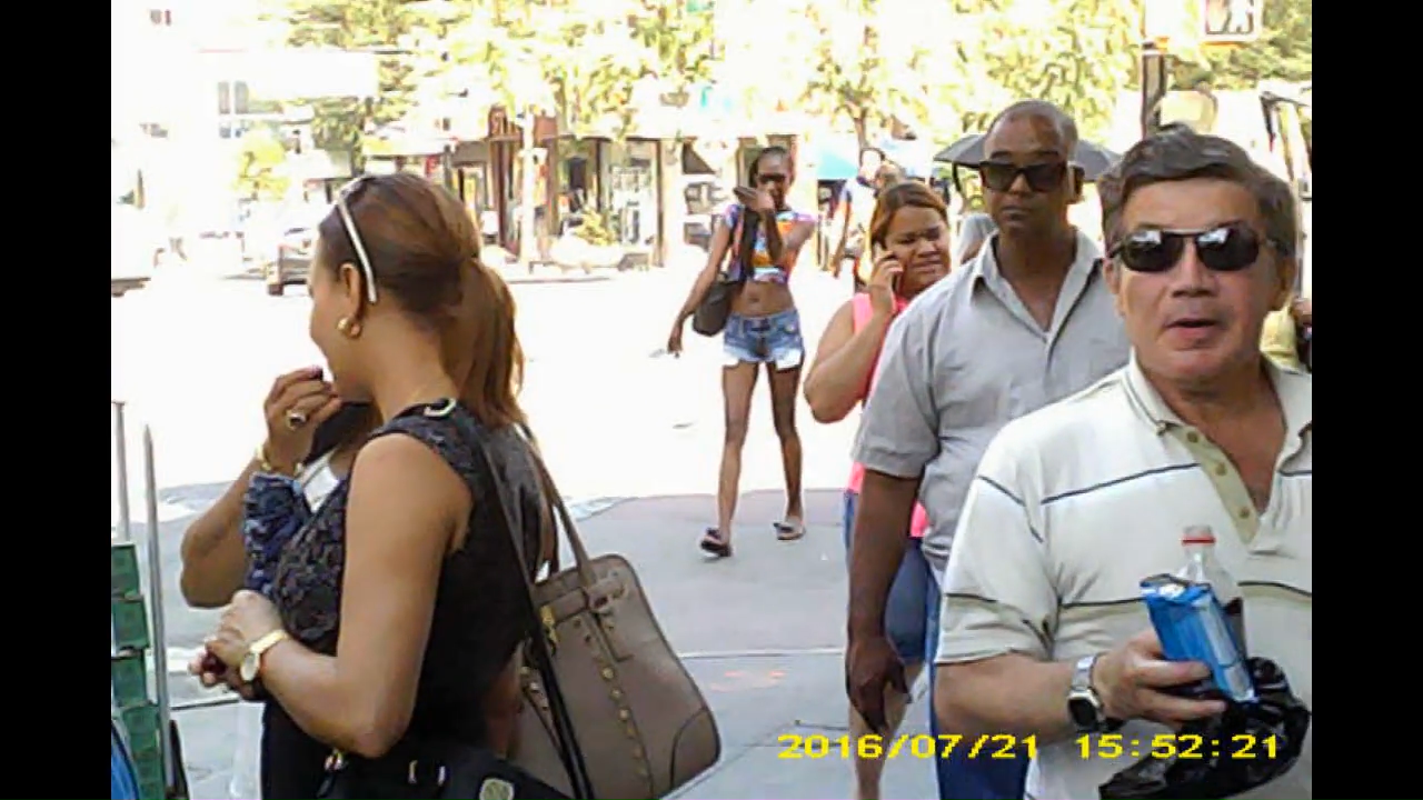 Two men with sun glasses, but light skinned latino man is holding something. Female with sun glasses now has hand over nose communicator.